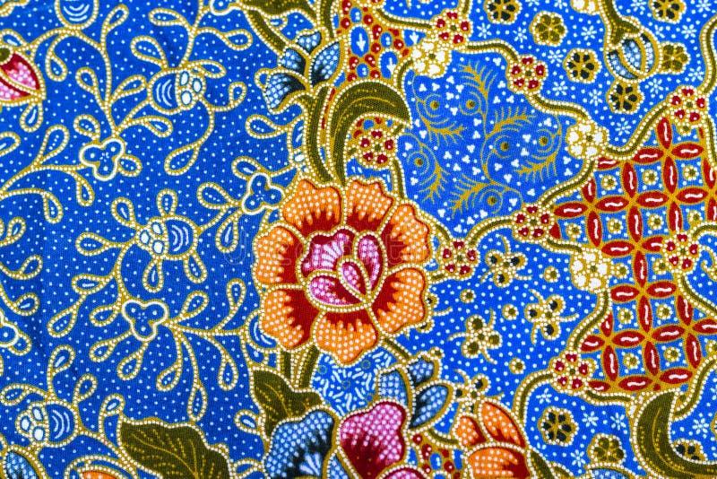 在蜡染布的橙色花纹花样 免版税图库摄影