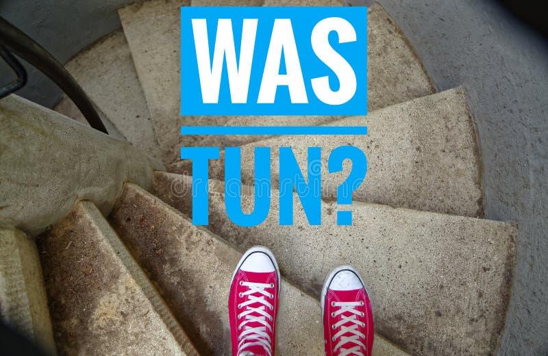 在螺旋形楼梯的红色运动鞋,当连同下坡题字用德语是大桶?用英语要做什么? 免版税库存图片