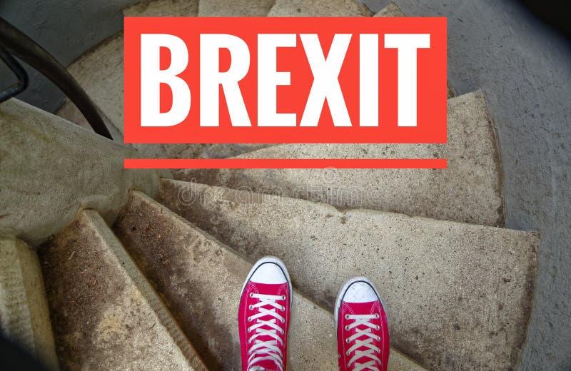 在螺旋形楼梯的红色运动鞋,当连同下坡题字象征撤退从时的大英国的Brexit 免版税库存图片