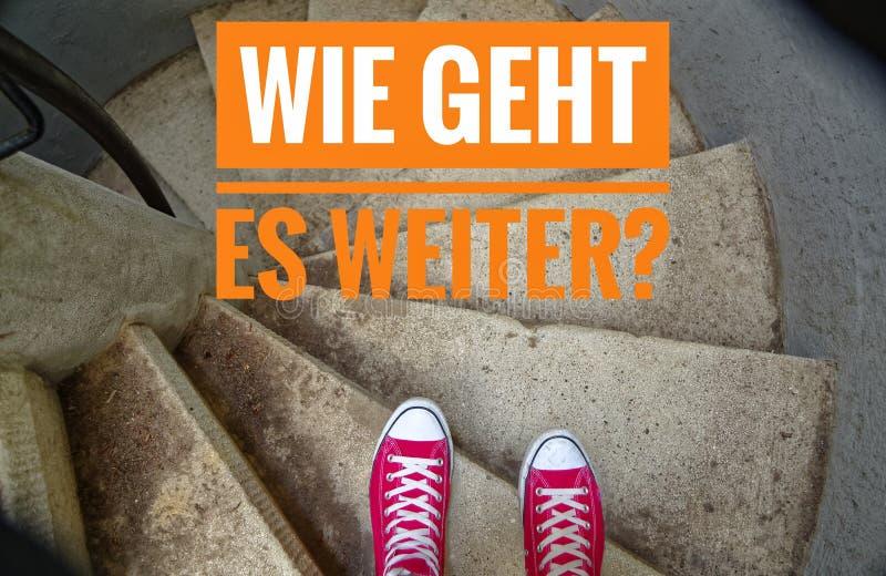 在螺旋形楼梯,当去下坡和时题字的红色运动鞋用德语Wie geht ES weiter ?用英语下一个是什么? 免版税库存图片