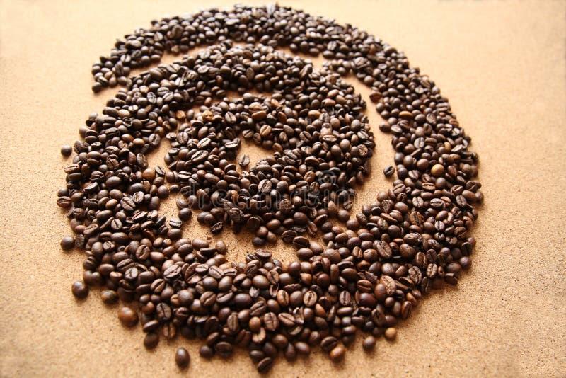 在螺旋形状的咖啡豆在木背景的 库存照片