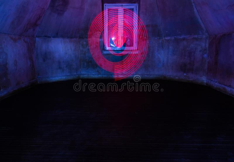在螺旋形状的抽象红色图在有一个闭合的窗口的一间空的屋子 库存图片