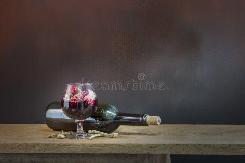 在血液玻璃和酒的头骨在木桌上 免版税库存照片