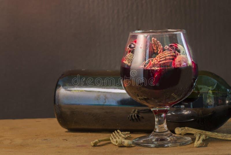在血液玻璃和酒的头骨在木桌上 免版税图库摄影