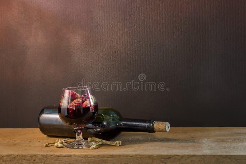 在血液玻璃和酒的头骨在木桌上 库存照片