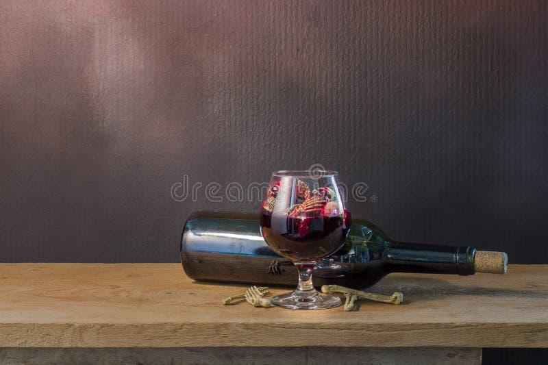在血液玻璃和酒的头骨在木桌上 免版税库存图片