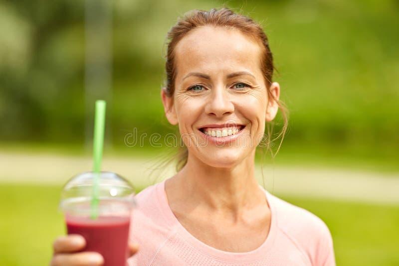 在行使以后的妇女饮用的圆滑的人在公园 免版税库存照片