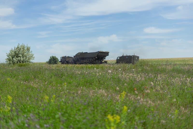 在行军的军用设备在反对天空蔚蓝的一个绿色领域中 免版税库存照片