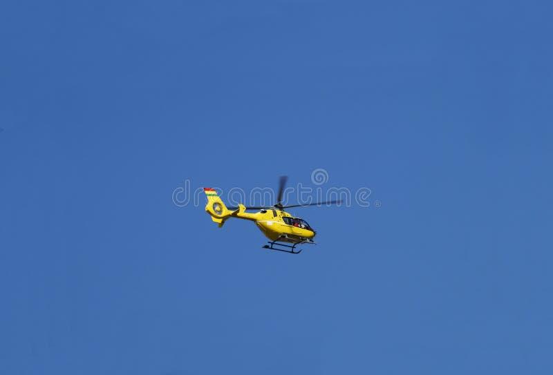 在行动,反对晴朗的天空的飞行的黄色抢救直升机 免版税库存图片