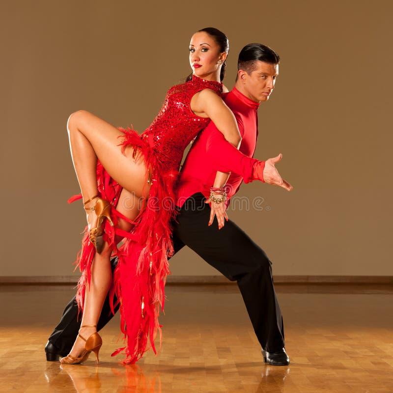 在行动-跳舞的狂放的桑巴的拉丁美州的舞蹈夫妇 免版税库存图片