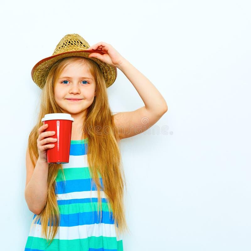 在行家样式的微笑的小女孩画象用红色咖啡g 库存图片