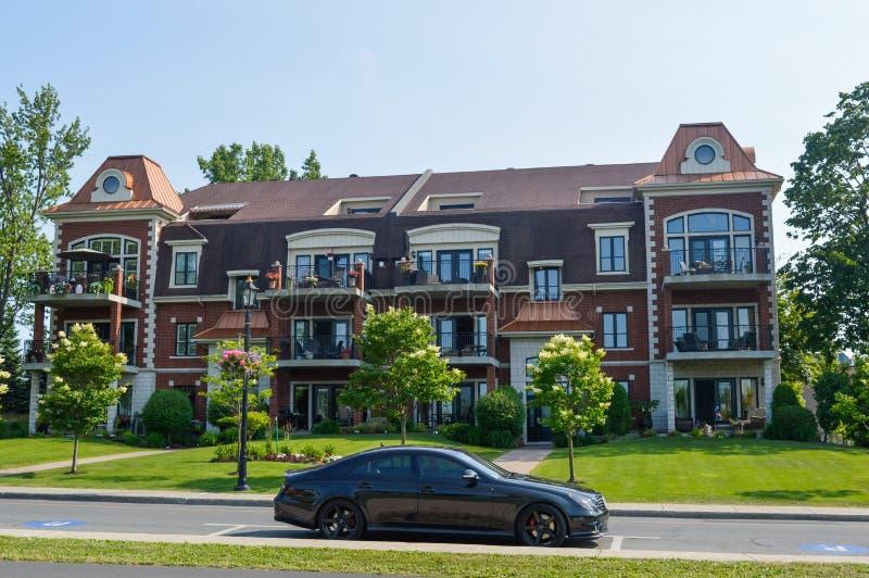 在街市的Chambly和一辆黑汽车的公寓房大厦 免版税库存照片
