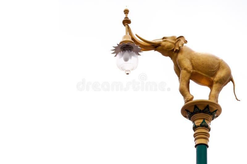 在街灯岗位孤立的金黄大象在白色背景 免版税库存图片