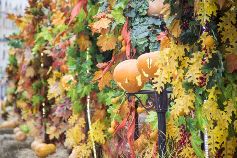 在街灯的南瓜 为与colorfull的秋天市场装饰的街道胡同离开 万圣夜秋天装饰 免版税库存照片