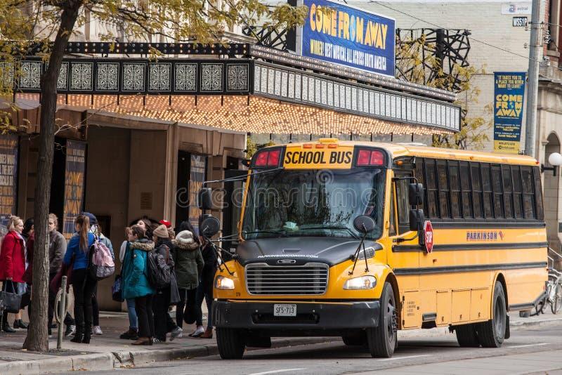 在街道上停放的北美洲黄色学校班车,等待的学生出去在多伦多一个市中心,安大略,加拿大 免版税库存图片