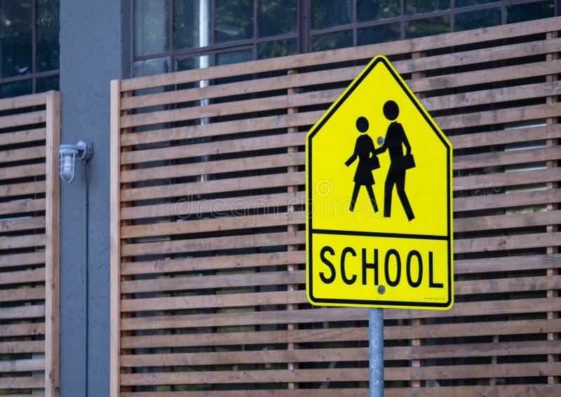 在街道上张贴的学校区域警报信号 免版税库存图片