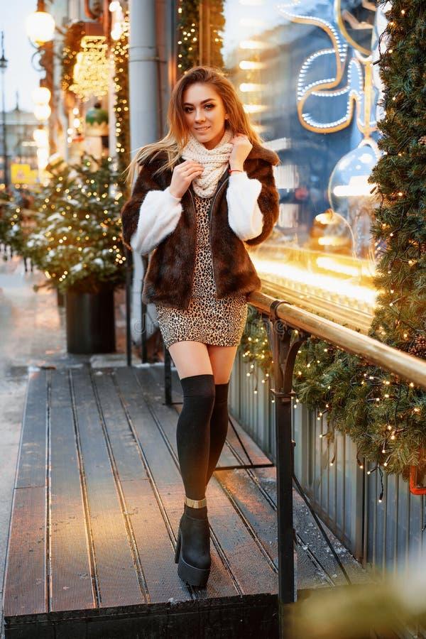 在街道上摆在优美地装饰的圣诞节窗口附近一美丽的年轻女人的画象,欢乐心情 免版税图库摄影
