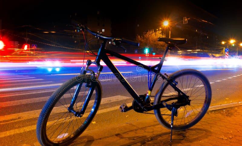 在街道上的一辆自行车在反对模糊的光背景的夜从汽车的,光在街道上落后 免版税库存照片