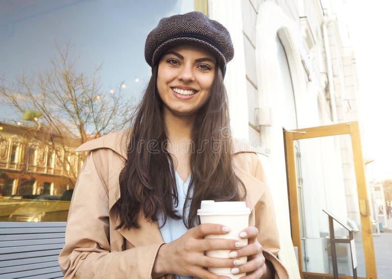 在街道上的俏丽的女孩立场有咖啡的由咖啡馆佩带的军用防水短大衣和盖帽的 免版税库存照片