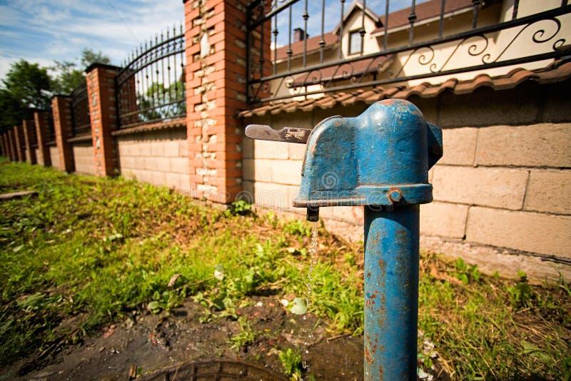 在街道上的储水塔水一条流动的小河在的篱芭和大厦 免版税图库摄影