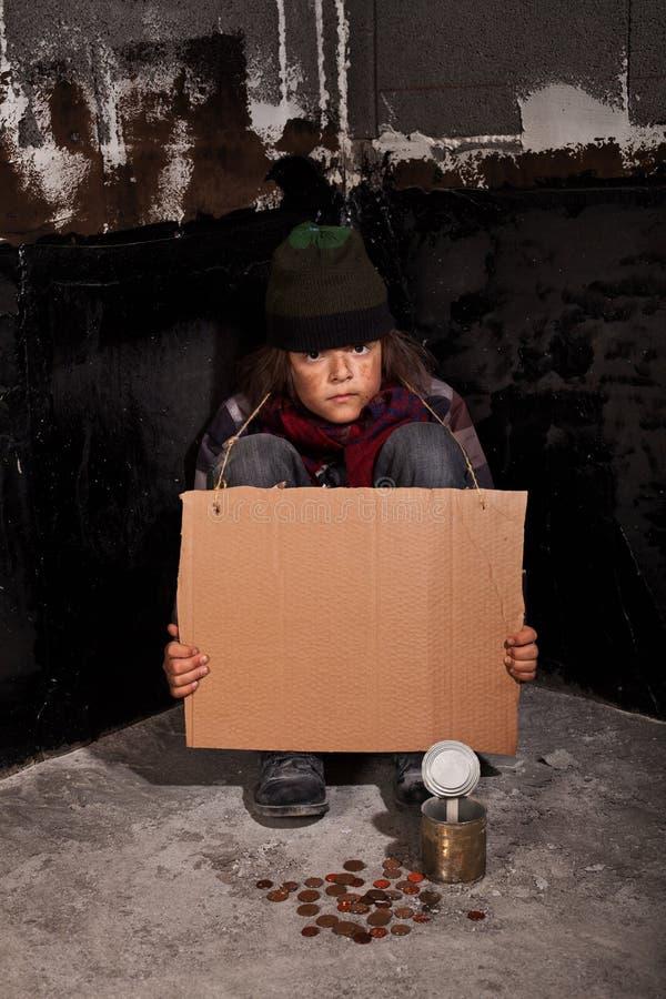 在街道上的可怜的叫化子孩子有空白的标志的 免版税图库摄影