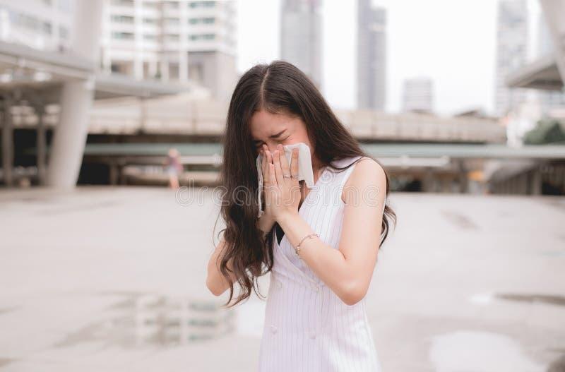 在街道上的妇女喷嚏,因为污染,年轻女性得到的鼻子过敏 库存照片