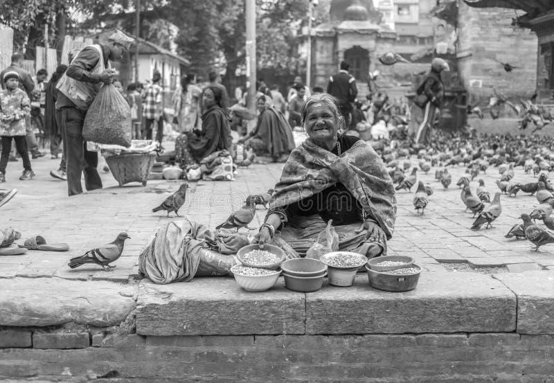 在街道上的尼泊尔妇女sellinh种子 免版税图库摄影