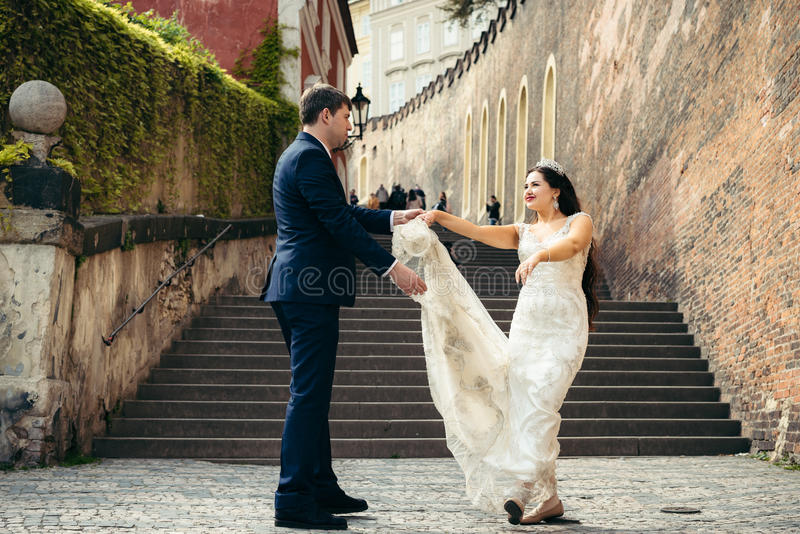 在街道上的愉快的跳舞新婚佳偶在布拉格 水平的特写镜头视图 图库摄影