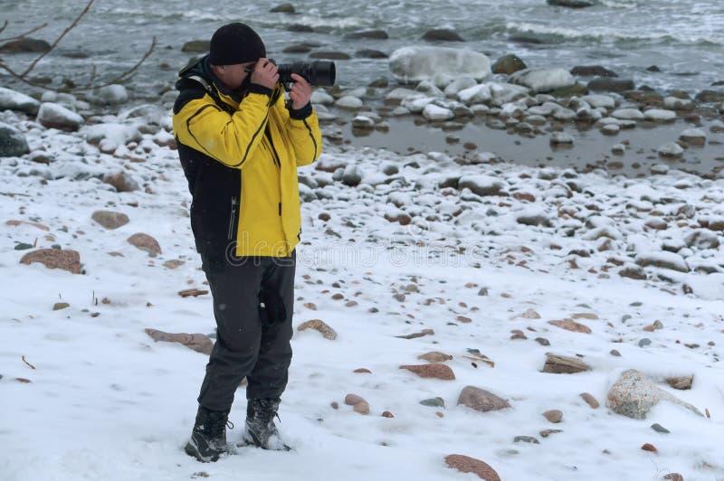 在街道上的摄影师在冷,拍摄在冬天,摄影师休假了他的手套 库存图片