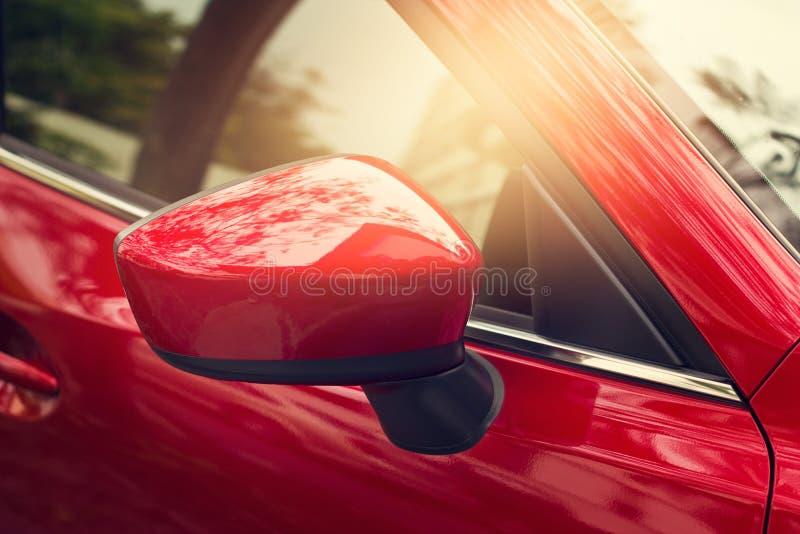 在街道上的旁边后视镜红色汽车 图库摄影