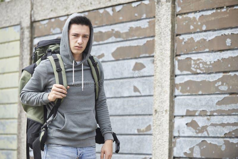 在街道上的无家可归的十几岁的男孩有背包的 库存图片