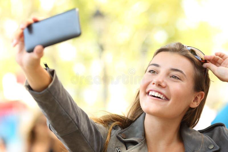 在街道上的时尚青少年的采取的selfies 免版税图库摄影