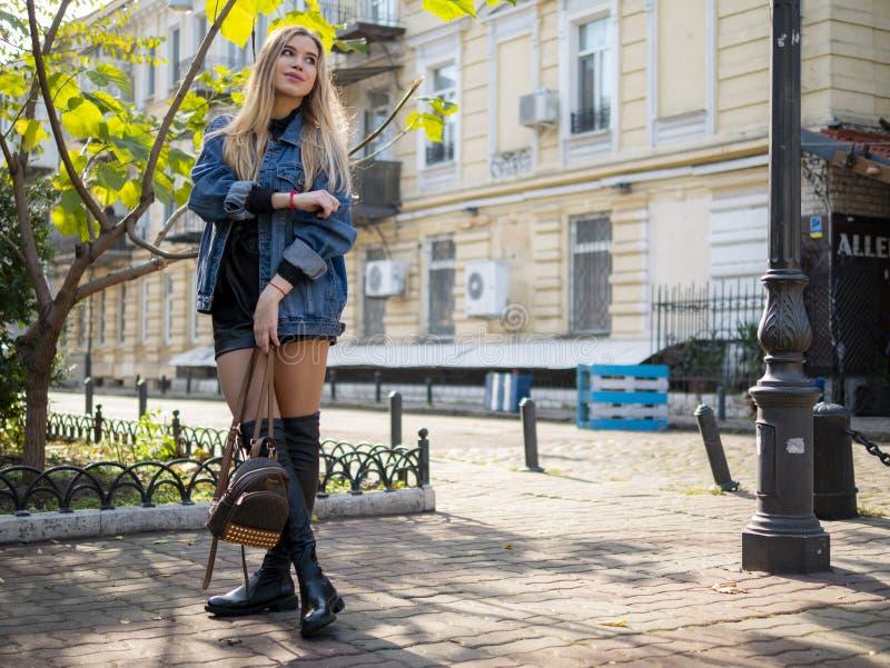 在街道上的有吸引力的女孩身分有她的在一件牛仔布夹克的头发的反对一个现代大厦的背景 库存照片