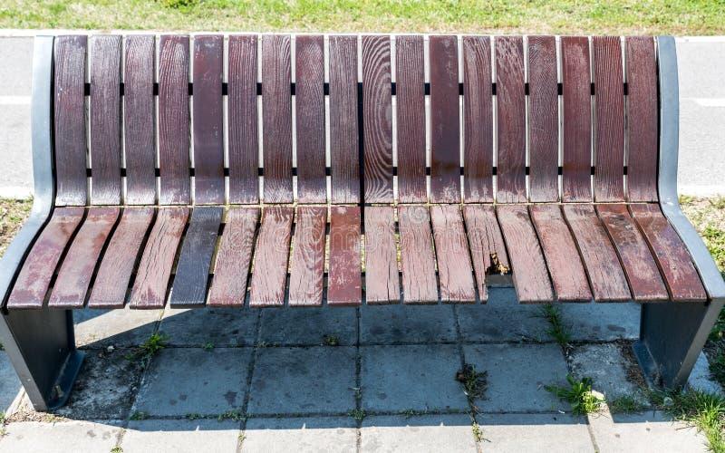 在街道上的残破和损坏的长木凳,故意破坏概念 库存图片