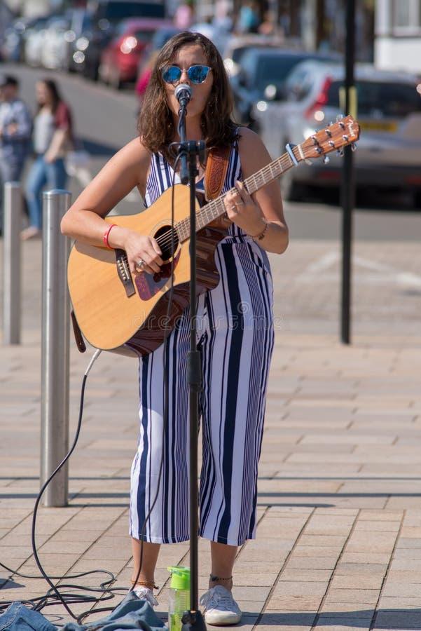 在街道上的深色头发的女歌手有太阳镜的和 库存图片