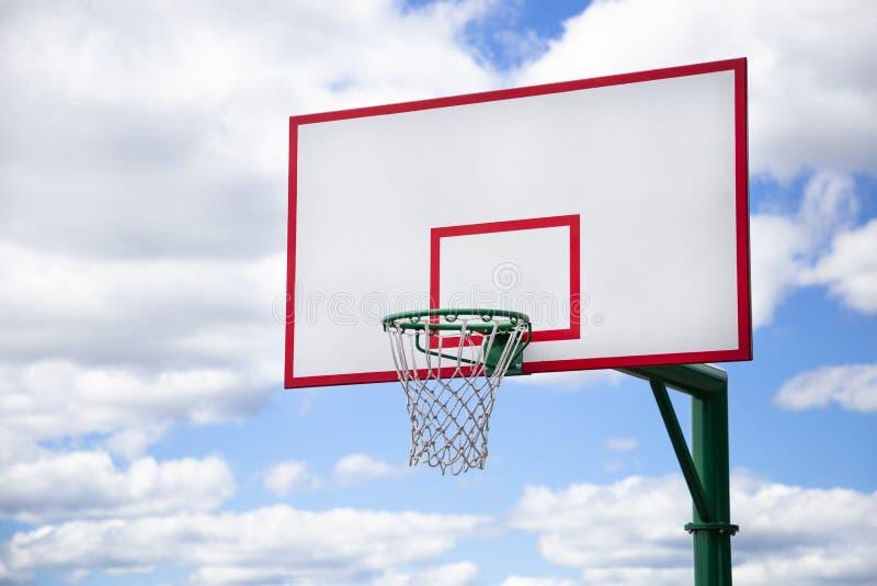 在街道上的篮球篮有在背景的蓝色多云天空的 户外运动活动和streetball概念 免版税库存图片