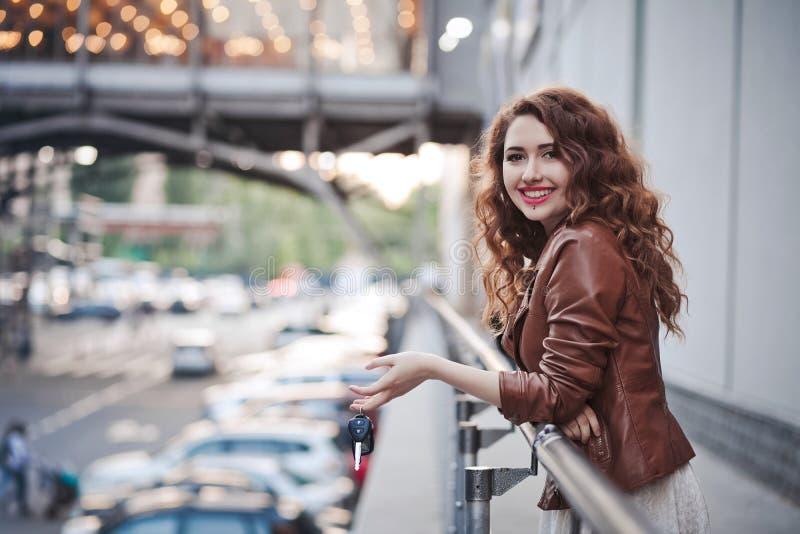 在街道上的美丽的女孩有从汽车的钥匙的 库存照片