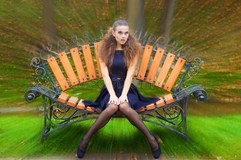 在街道上的美好的女孩秋天天有在一件黑礼服的幻想构成的有大嘴唇的坐长凳 库存照片