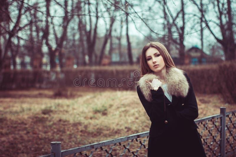 在街道上的美好的少妇皮大衣穿戴 免版税库存图片