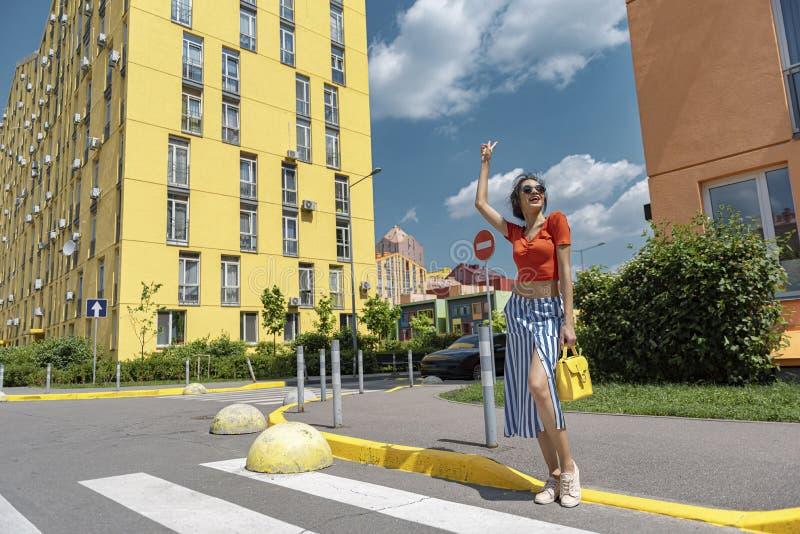 在街道上的美好的年轻女人身分和显示胜利姿态 免版税库存照片
