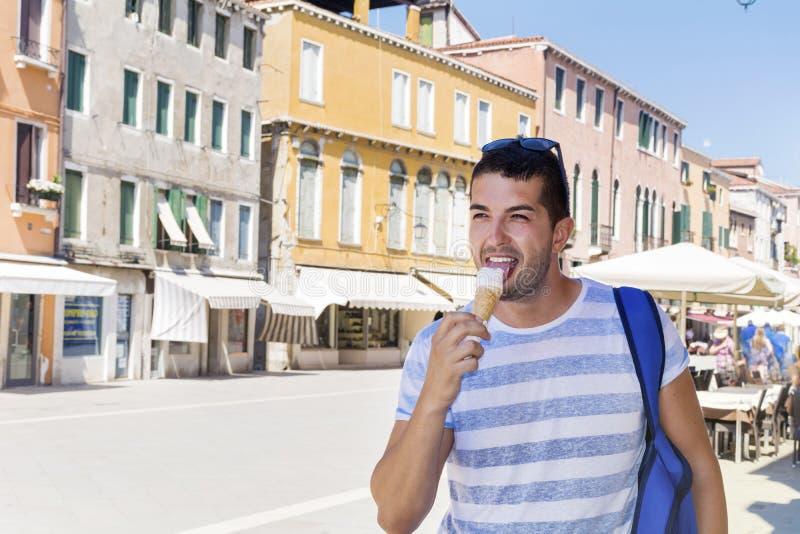在街道上的英俊的年轻食人的冰淇凌在威尼斯 图库摄影
