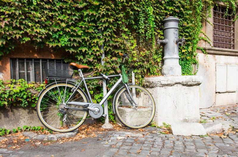 在街道上的饮用的轻拍附近停放的自行车在罗马 免版税库存图片