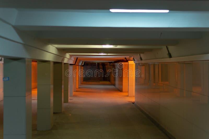 在街道下的地下过道在城市 有恶劣的照明设备的空的地下过道 库存照片
