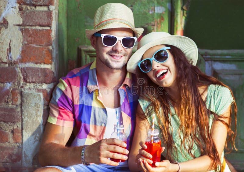 在街道佩带的帽子和太阳镜的愉快的年轻夫妇 免版税库存照片