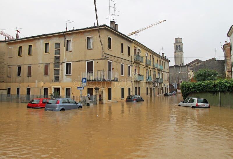 在街道和路的汽车由洪水的泥淹没了 库存照片