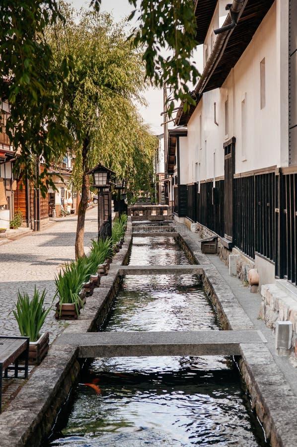 在街道和Hida F小自然小河上的老日本房子  免版税库存照片