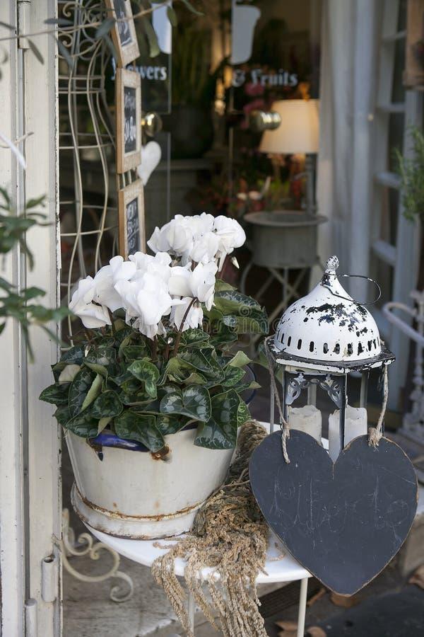 在街道咖啡馆的表用在一个罐和一盏灯的仙客来装饰圣诞节的 免版税库存照片