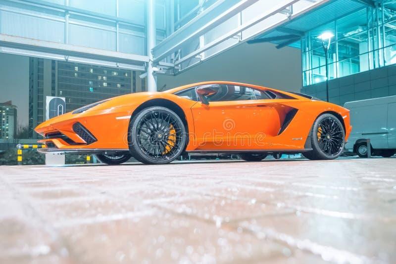 在街道城市停车场的Lamborghini Aventador橙色夜 荷兰男人飞行堡垒保罗・彼得・彼得斯堡餐馆俄国圣徒 2018年3月13日 免版税库存图片