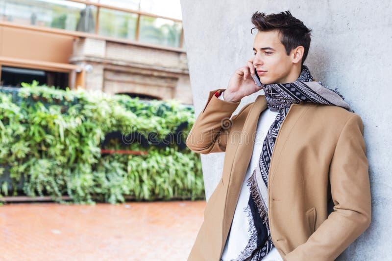 在街道的年轻人佩带的冬季衣服使用他的电话 有现代发型的年轻人与外套、蓝色牛仔裤和T恤杉 免版税库存照片