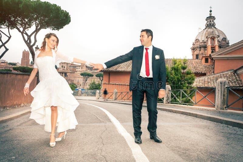 在街道的愉快的新婚佳偶夫妇在市中心 图库摄影